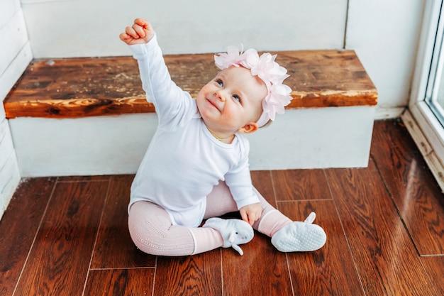 Een klein lachend babymeisje van een jaar oud met een lentekrans die op de vloer ligt in een heldere lichte woonkamer bij het raam en speelt met gerberabloemen. gelukkig kind thuis spelen. jeugd concept