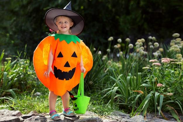 Een klein lachend meisje in een pompoenkostuum en met een snoepzakje viert halloween