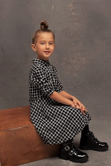 Een klein lachend meisje op een donkere achtergrond in de studio. kinderen zijn modellen. gelukkige jeugd.