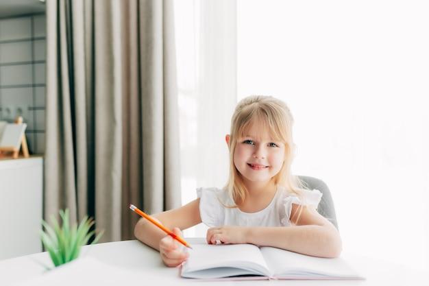 Een klein lachend meisje zit aan de tafel en schrijft in een wit notitieboekje. onderwijs concept. thuisonderwijs. huiswerk. lachend gezicht.