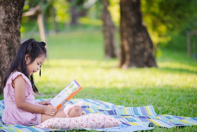 Een klein leuk meisje dat een boekzitting onder de boom leest