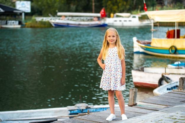 Een klein meisje aan de kade bij de rivier in een witte zomerjurk in de stad dalyan. kalkoen.
