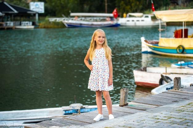 Een klein meisje aan de kade bij de rivier in een witte zomerjurk in de stad dalyan. kalkoen