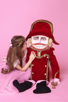 Een klein meisje als schoonheid ballerina op roze lange jurk met notenkraker op roze studio