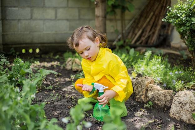 Een klein meisje assistent in de tuin in een gele regenjas met vuile handen met een spuitpistool planten water geven