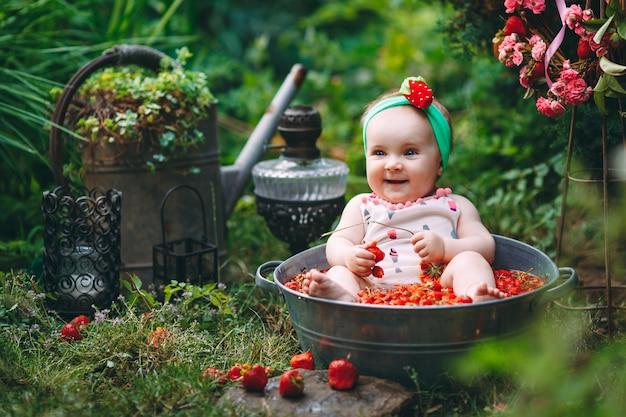 Een klein meisje baadt in een bassin met aardbeien in de tuin.