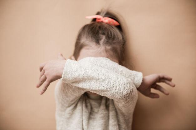 Een klein meisje bedekt haar gezicht met haar handen. selectieve aandacht