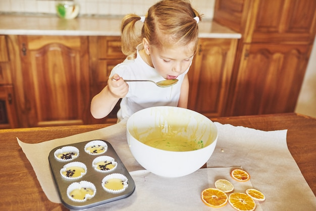 Een klein meisje bereidt een deeg voor muffins voor.