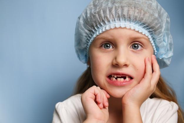 Een klein meisje bij de tandarts toont een tandeloze mond.