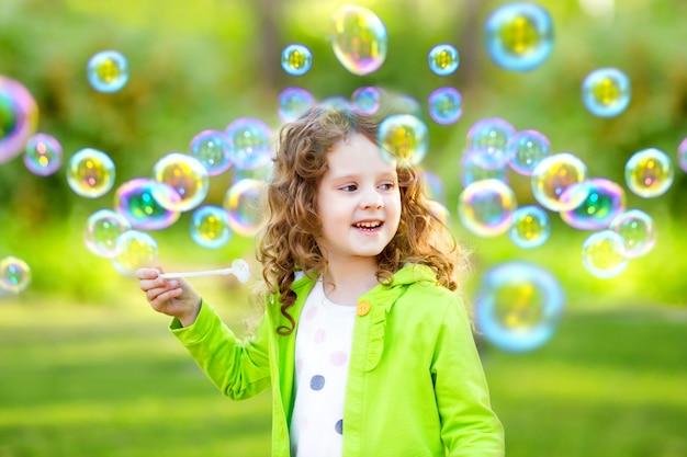 Een klein meisje blaast zeepbels, springt de mooie krullende baby van het de lenteportret op.