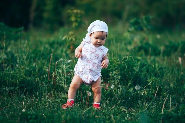 Een klein meisje blaast zeepbels, springt het mooie oude éénjarig jonge geitje van het de lenteportret op