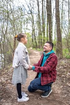 Een klein meisje communiceert met haar vader in het bos voor een wandeling, hand in hand.