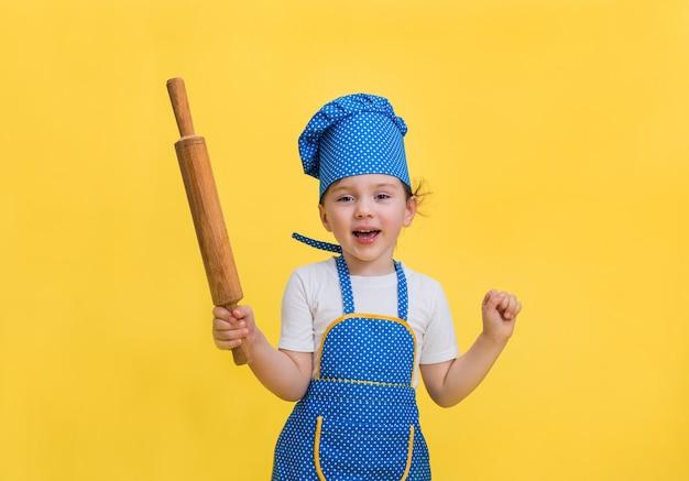 Een klein meisje dansen in een keukenschort en hoed met een deegroller in haar hand op een gele ruimte. een mooi meisje in een blauw en geel schort en een koksmuts. op zoek .