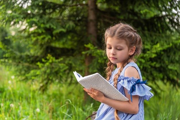 Een klein meisje dat een boek leest in een groen park