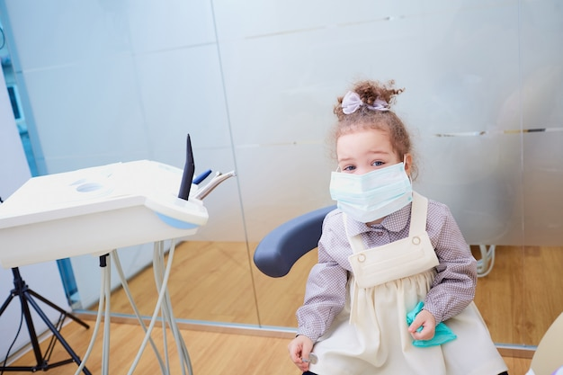 Een klein meisje dat een masker in het kantoor van de tandarts draagt