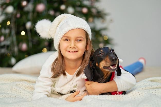 Een klein meisje dat haar hond dichtbij de kerstboom houdt