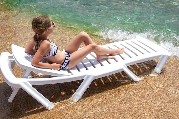 Een klein meisje dat op een chaise longue ligt kijkt naar de zee