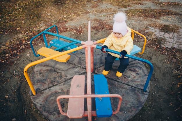 Een klein meisje dat speelt op de speelplaats van de kinderstad. een klein kind rijdt de heuvel af, op de carrousel, klimt de touwen op. concept van de entertainmentindustrie, familiedag, kinderparken