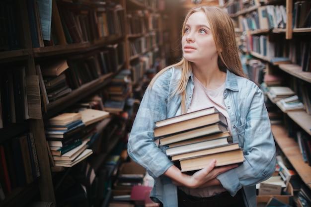 Een klein meisje dat zich in een grote oude boekhandel bevindt en veel boeken in haar handen houdt. ze is op zoek naar een ander boek om mee te nemen. jonge schoonheid ziet er dromerig uit.