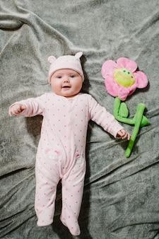 Een klein meisje, de pasgeboren baby, ligt op het oppervlak van een grijze zachte deken op het bed, houdt een bloemenspeeltje voor moeder vast en glimlacht. fotosessie 4 maanden. plat leggen. bovenaanzicht.