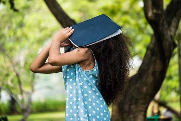 Een klein meisje die betrekking hebben op gezicht met een boek in een park
