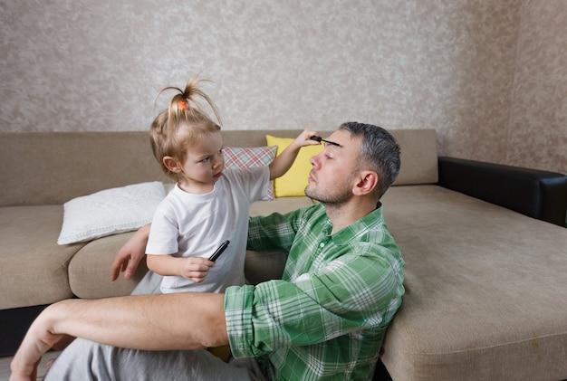 Een klein meisje doet tijdens spelletjes samen make-up bij haar vader