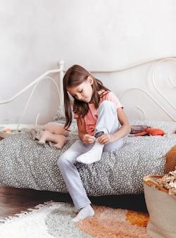 Een klein meisje draagt sokken zittend op een bed in haar slaapkamer. de jongen gaat naar school. onafhankelijke kinderen
