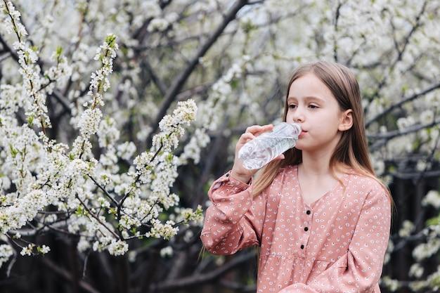 Een klein meisje drinkt schoon zoet water uit een plastic fles in de buurt van een bloeiende boom in de tuin.