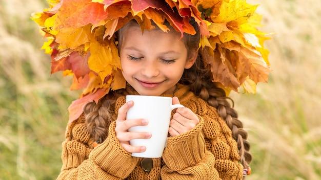 Een klein meisje drinkt thee op een herfstdag.