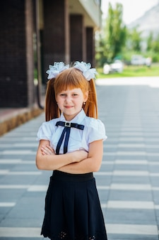 Een klein meisje, een basisschoolleerling, staat op straat met haar handen gevouwen. portret van een schoolmeisje met rood haar. terug naar school.