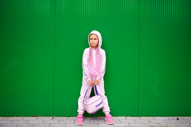 Een klein meisje, een schoolmeisje, in een roze jumpsuit en afro-staartjes op haar hoofd, houdt een rugzak tussen haar benen.