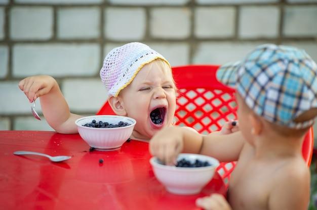 Een klein meisje en een jongen eten bosbessen aan tafel