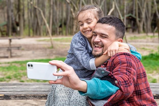 Een klein meisje en een vader worden in het vroege voorjaar op de voorkant van de mobiel in het park gefotografeerd.