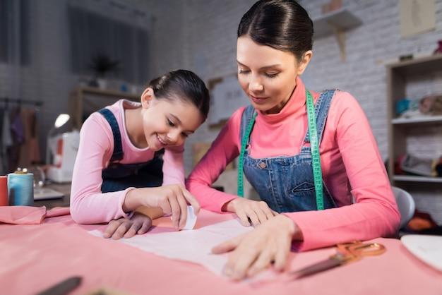 Een klein meisje en een volwassen vrouw die kleren passen