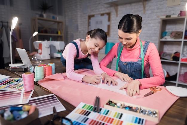 Een klein meisje en een volwassen vrouw die op kleren probeert