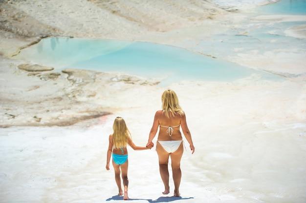 Een klein meisje en haar moeder in zwemkleding lopen op de witte berg in de stad pamukkale. kalkoen