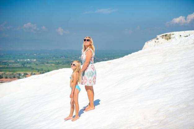 Een klein meisje en haar moeder lopen op de witte berg in de stad pamukkale. kalkoen