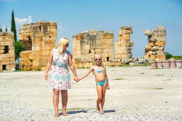Een klein meisje en haar moeder wandelen in de oude ruïnes in de stad pamukkale. kalkoen.