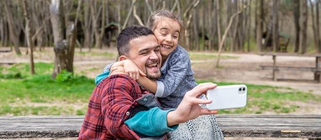 Een klein meisje en papa worden in het vroege voorjaar gefotografeerd op de camera aan de voorkant in het park.
