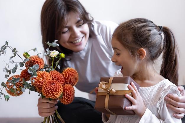 Een klein meisje geeft haar moeder een cadeau en een boeket bloemen