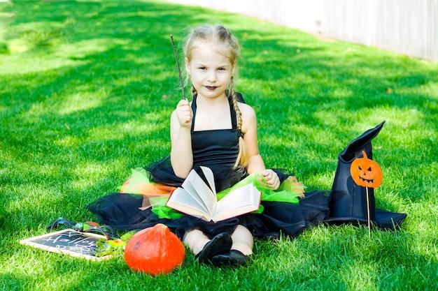 Een klein meisje gekleed in een heksenkostuum, een zwarte hoed en zwarte lippenstift op haar lippen zit met een boek en houdt een toverstaf vast. halloween.