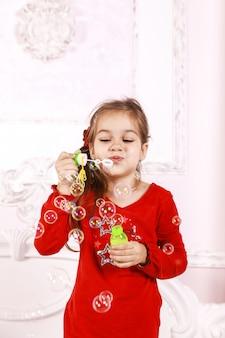 Een klein meisje gekleed in een rode pyjama speelt binnenshuis met bubbels