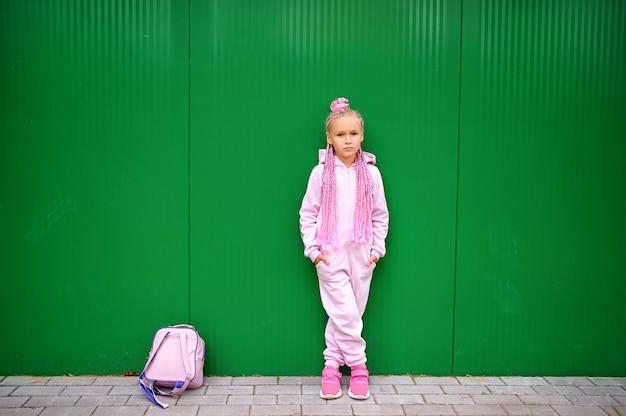 Een klein meisje gekleed in een roze pak staat tegen een groene muur.