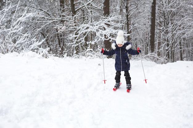 Een klein meisje glijdt de helling af in rode plastic ski's.