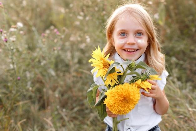 Een klein meisje glimlachend met gele zomerbloemen op een groene achtergrond