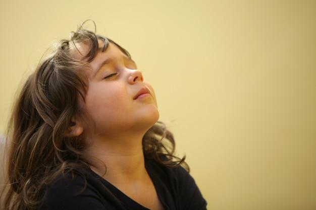 Een klein meisje haalt diep adem en glimlacht