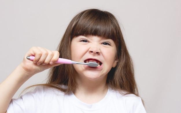 Een klein meisje haar tanden poetsen met een felgekleurde tandenborstel