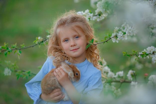 Een klein meisje heeft een konijn in haar handen een bloeiende boom in de lente