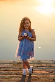 Een klein meisje heeft een toetje in haar handen en wil het graag eten.