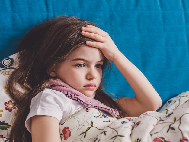 Een klein meisje heeft griep en ligt thuis onder een deken